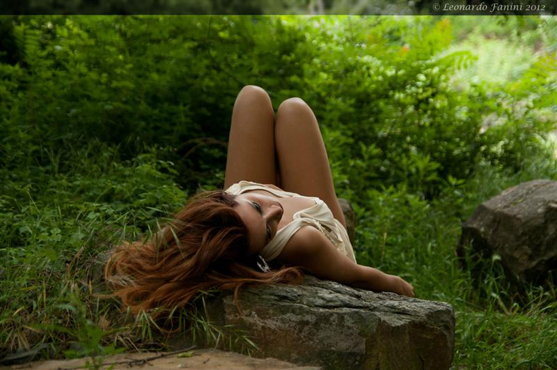 red head girl laying down on a rock in the wild
